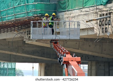 JOHOR, MALAYSIA -APRIL 12, 2016: Construction workers standing in the mobile crane bucket while working at high level in the construction site in Malaysia.