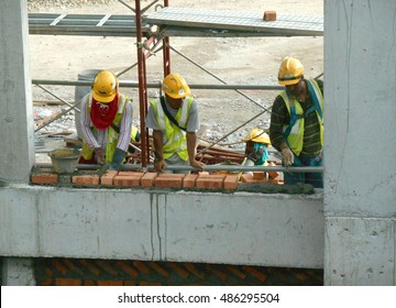 JOHOR, MALAYSIA -AUGUST 05, 2016: Bricklayer lay clay bricks to form building walls at the construction site.