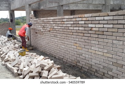 JOHOR, MALAYSIA -DECEMBER 05, 2016: Bricklayer lay clay bricks to form building walls at the construction site.