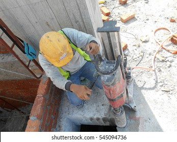 JOHOR, MALAYSIA -DECEMBER 06, 2016: Concrete coring work by construction worker. He using coring machine to drill a hole to the concrete.