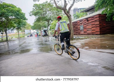 JOHOR, MALAYSIA - December 18, 2017: A security guard used a bicycle of the bike sharing company Obike. Image contain certain grain or noise and soft focus.