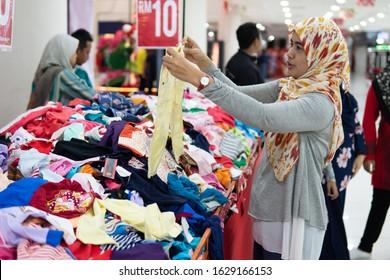 Johor Malaysia - Jan 14,2020 - A asian woman choosing a shirt during shopping  festival in a local mall