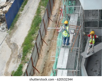 JOHOR, MALAYSIA -JANUARY 07, 2017: Construction workers working  at the construction site. Using scaffolding as temporary platform to work. They are required to wear proper safety gear.