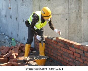 JOHOR, MALAYSIA -JANUARY 13, 2017: Bricklayer lay clay bricks block to form building walls at the construction site.