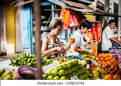 JOHOR, MALAYSIA, JUNE 4 2015: Wet Market. A Chinese aunt is picking fruit. In addition, there are other buyers in the market.