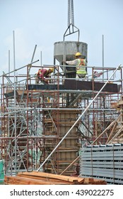 JOHOR, MALAYSIA -MAY 06, 2016: A group of construction workers pouring concrete using concrete bucket into the column form work at the construction site.