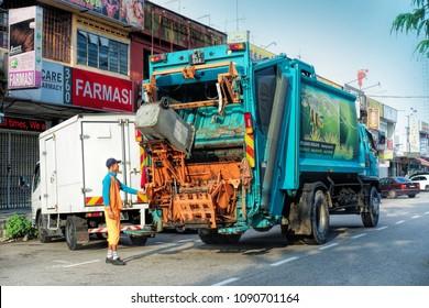 JOHOR, MALAYSIA - MAY 5, 2018: Worker of urban municipal recycling garbage collector truck loading waste and trash bin in Johor Bahru Street, Johor, Malaysia. Taken on May 5, 2018.