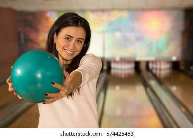 Join me in game. Gorgeous happy young woman smiling holding out a bowling ball at the club bowling alleys on the background copyspace youth carefree active sports happiness lifestyle game concept