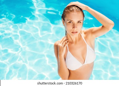 Join me in the pool! Top view of attractive young woman in white bikini standing at the pool and looking at camera