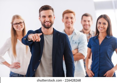 Join our team! Beautiful young woman showing her thumb up and smiling while group of happy young people standing on background and smiling