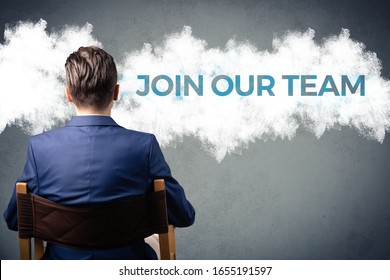 Join our team. Confident businessman with arms crossed standing next to sign on the wall. Job search concept.