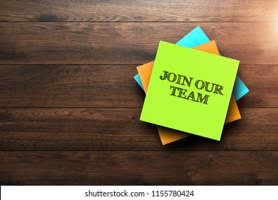 Join Our Team, the phrase is written on multi-colored stickers, on a brown wooden background. Business concept, strategy, plan, planning.