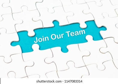 Join Our Team texts with white jigsaw puzzle board on blue background. Business concept.
