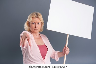 Join the protest. Fair-haired middle-aged woman holding a banner and pointing at the camera as if asking to join in the protest