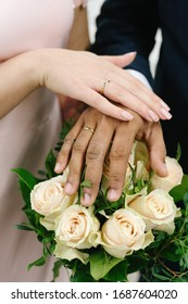 The joined hands of the bride and groom at a wedding. Wedding rings on the fingers of the newlyweds. Hands close up.