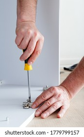 Joiner collects furniture using hand tools screwdriver. Furniture assembly using screwdriver. Moving, home improvement, furniture repair and renovation. Carpenter collects a white furniture cupboard