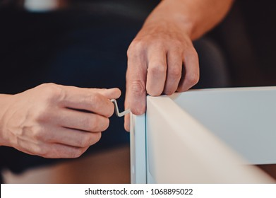 Joiner collects a new baby cot with a hand tool. carpenter collects a cot. collects the walls of the crib using a hand hexagon. fixes the pendulum of a cot. hands view