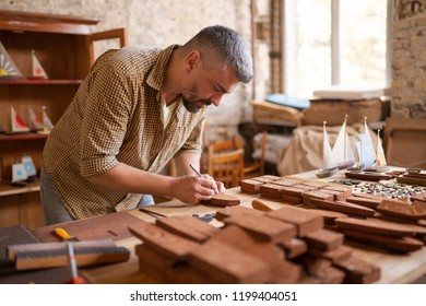 A joiner during his work with wood. In the workshop of a wood carpenter. Small blanks of wood for future boats.
