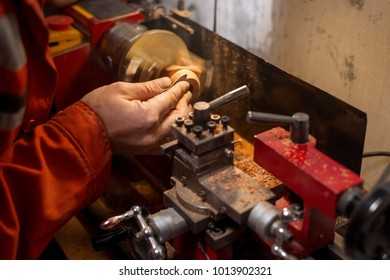 Joiner is grinding wooden block with sandpaper while the lathe is on. The craft of wood turning.