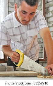 a joiner sawing a plank