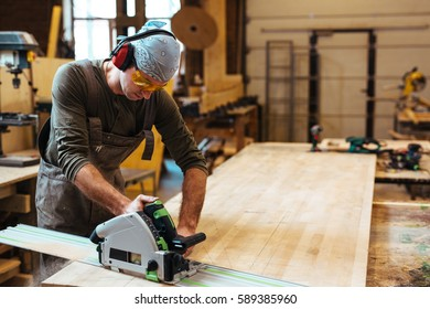 Joiner working with wood-router on workbench