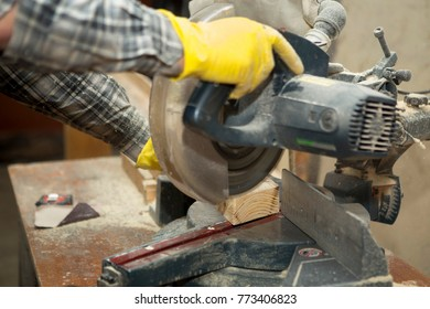 Joiner works on the machine with the wooden product manufacturing. The carpenter cuts the wood of various configurations on the machine tool