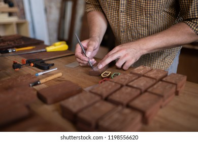 A joiner's table. Close-up view of joiner's hands while he holds a pencil and works with wood.