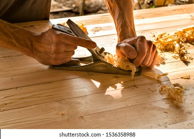 Joinery. Planing a natural wood furniture panel with a manual planer. Hands with a planer.