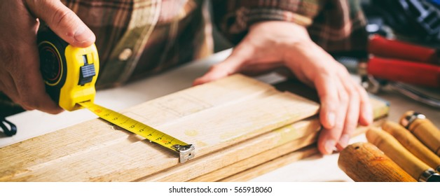 Joinery tools. Carpenter holding a measure tape on the work bench