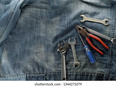 Joinery tools on labor day concept. Work shoes, spanner, adjustable wrench, wire cutters, pliers, screwdriver, isolated on labor jacket.