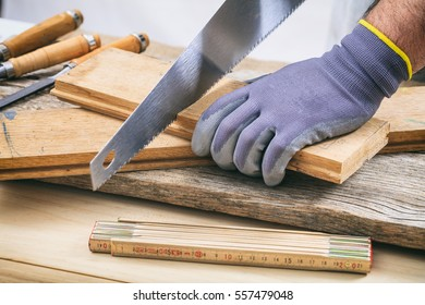 Joinery workshop. Man with gloves working with a hand saw