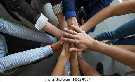 Joining leader. Close up top view of diverse people business partners friends colleagues stacking palms in pile as symbol of racial and gender equality, unity, support of good proposal project startup