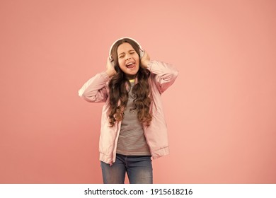 Joining in a song. Small girl sing to song pink background. Little child do vocal on song. Emotional singer. Enjoying song playing in headphones. Karaoke and entertainment. Singing along to tune.