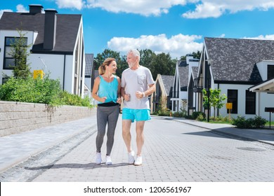Joining wife. Bearded mature husband joining his beautiful slim wife while running near their house in the morning