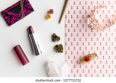 Joint, buds and edibles with pink and red accessories on top of a pink pineapple background.