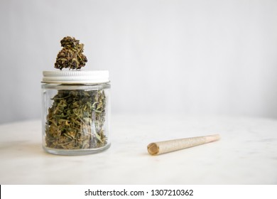 Joint and Cannabis Glass Jar on White Marble - Cannabis Dispensary Products