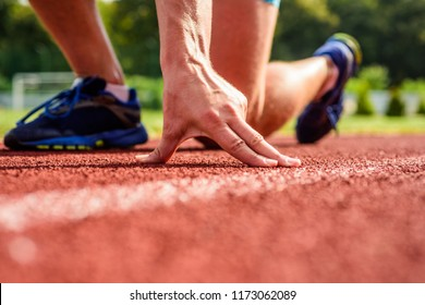 Joint care for runners. Hand of sportsman on running track low start position. Runner ready to go close up. Ultimate remedies. Flexibility is ability to stretch joint to limit of range movement.