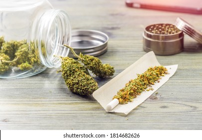 Joint essentials on wooden table flower buds paper filter grinder, medical or recreational marijuana concept
