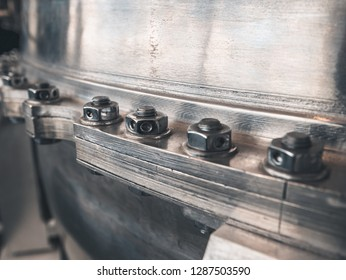 Joint of flanges by bolts and nuts, close up. Flanged vacuum equipment. Shiny metal surface as abstract industrial background