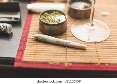 Joint, grinder, cannabis buds, and related items on a table.