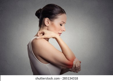 Joint inflammation indicated with red spot on female's elbow. Arm pain and injury concept. Closeup portrait woman with painful elbow on gray background