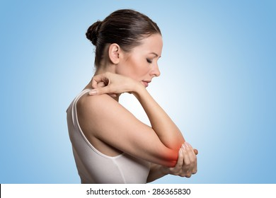 Joint inflammation indicated with red spot on female's elbow. Arm pain and injury concept. Closeup portrait woman with painful elbow on blue background