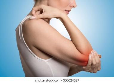 Joint inflammation indicated with red spot on female's elbow. Arm pain and injury concept. Closeup cropped portrait woman with painful elbow isolated on blue background