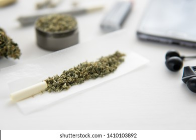 joint with marijuana, Cannabis buds on black table, close up, grinder with fresh weed,