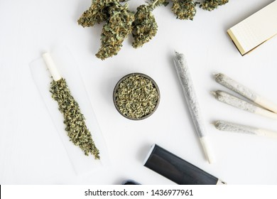 joint with marijuana, grinder with fresh weed, Cannabis buds on black table, close up,