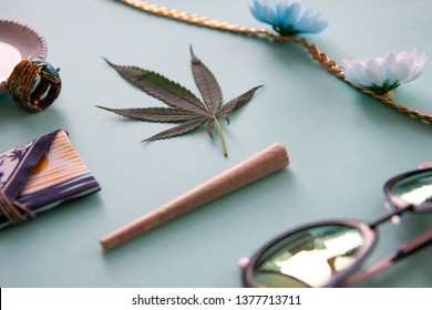 Joint and Marijuana Leaf on a Blue Background with Flowers, Gold Ring, Sunglasses and Bud Pouch for Festivals