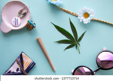 Joint and Marijuana Leaf on a Blue Background with Flowers, Gold Ring, Sunglasses, Earrings, Pin and Bud Pouch for Festivals