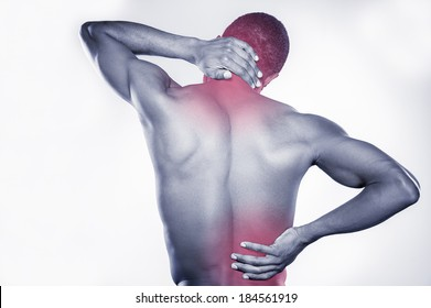 Joint pain. Rear view of young muscular African man touching his neck and hip while standing against grey background