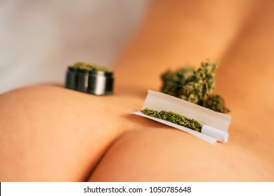 joint weed Cannabis buds on the girl's ass grinder rolled marijuana. The concept of sex and marijuana. themed weed and sex