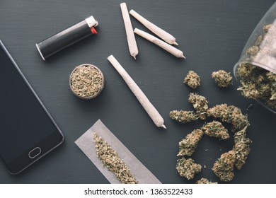 joint with weed, Cannabis buds on black table, close up, grinder in hand with fresh marijuana,